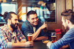 people, men, leisure, friendship and communication concept - happy male friends drinking beer at bar or pub