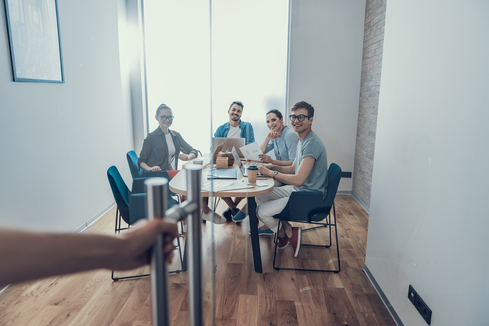 Full length portrait of four happy coworkers sitting at wooden desk and looking on glass door. Copy space in right side