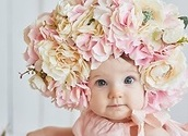 Sweet funny baby in hat with flowers. Easter greeting card, copyspace for your text. Poster for Easter holiday. Congratulations on Mother's Day. Cute baby girl 6 months wearing flower hat
