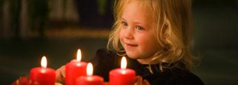 Mädchen vor einem Adventkranz