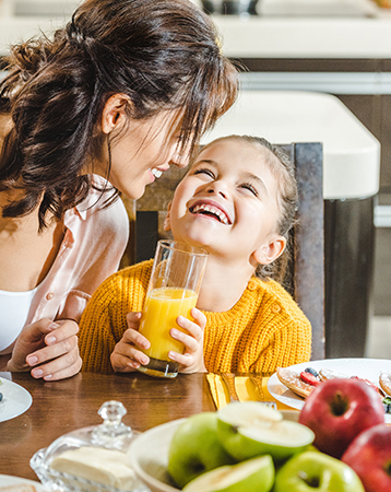 cheerful mother with daughter sitting at table with fresh juice and pancakes with berries at kitchen