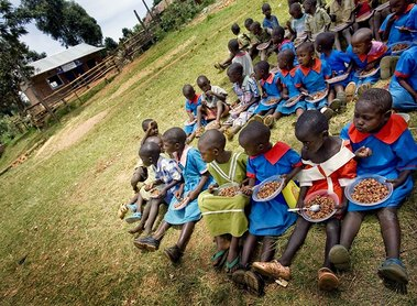 A group of school children eat a meal outside  their newly constructed kitchen at their school in Enchoro, Western Kenya on 19th February, 2009. Mary's Meals, a Scottish NGO, alongwith Tescoes supermarket sponsor each child at the school to have one